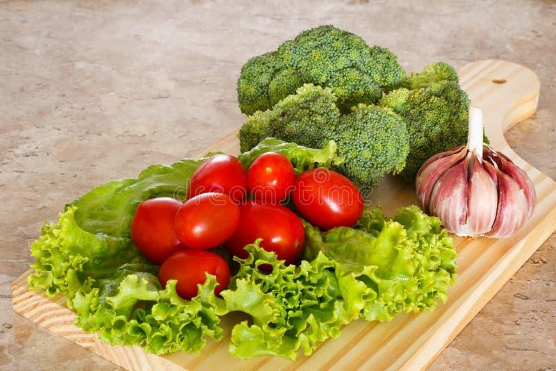 Brocoli, tomates et ail frais sur le conseil en bois photos libres de droits