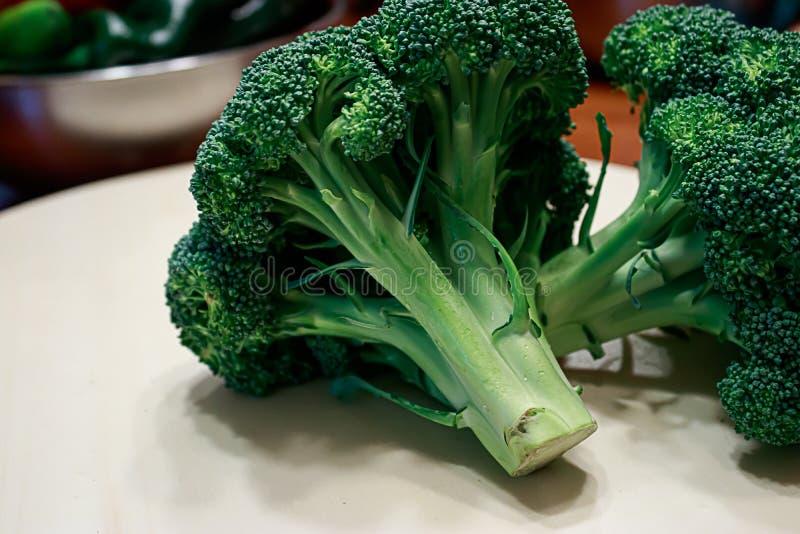 Brocolli, das auf dem runden Schneidebrett frisch und ungekocht sitzt stockfotografie