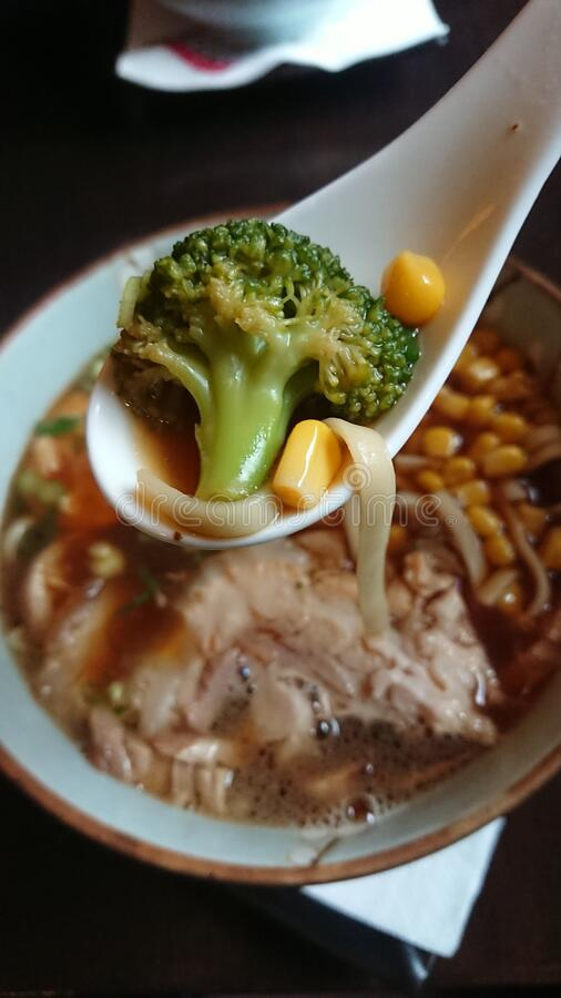 Brocolli held in spoon over a fresh and delicious Ramen japaneese pork soup royalty free stock image