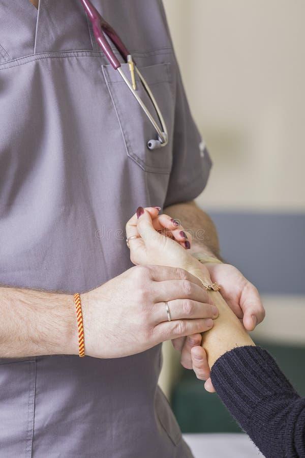 Brodaci doktorscy jest ubranym szkła sprawdzają pacjenta puls zdjęcie royalty free