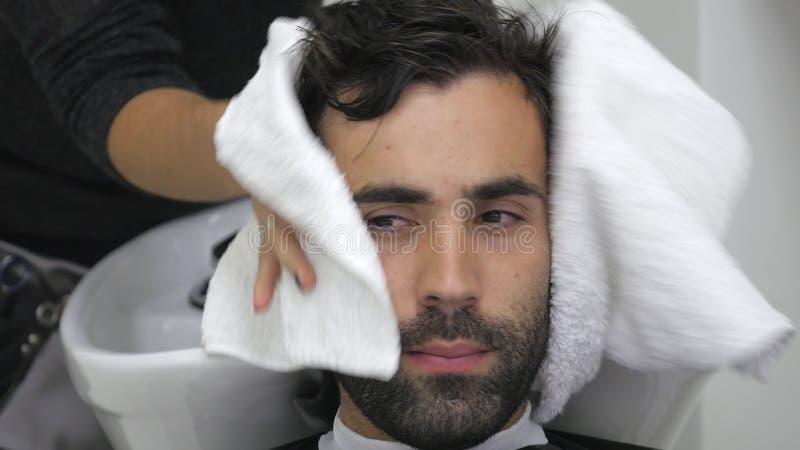 Brodaci młodzi człowiecy wycierają głowę z ręcznikiem Fryzjery obrazy royalty free
