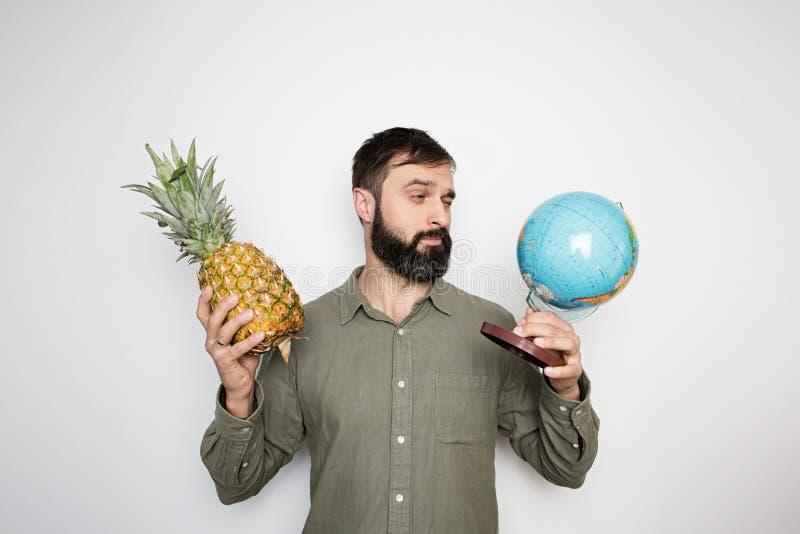 Brodata mężczyzny mienia kula ziemska i ananasowy tropikalny owocowy sok na tło ścianie obraz stock