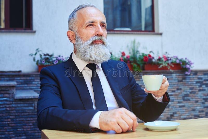 Brodata męska pije kawa podczas gdy siedzący fotografia stock
