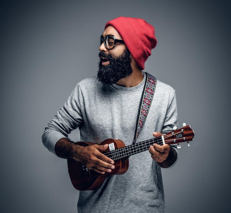 Brodata modniś samiec w czerwonym kapeluszu bawić się na ukulele zdjęcia royalty free