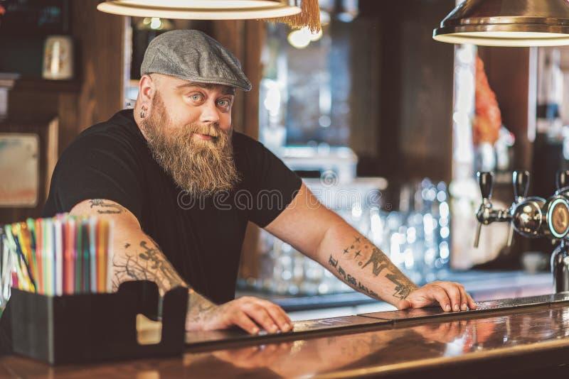 Brodata otyła facet pozycja przy miejscem pracy w pubie fotografia stock