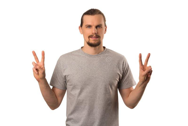 Brodatego atrakcyjnego caucasian faceta hoding ręki z zwycięstwo znakiem odizolowywającym na bielu zdjęcia stock