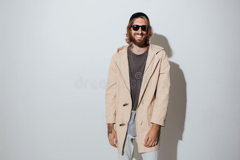 Brodatego modnisia szczęśliwy mężczyzna jest ubranym okulary przeciwsłonecznych obraz royalty free