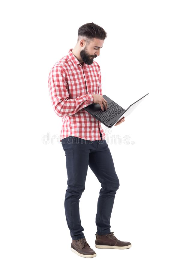 Brodatego nowożytnego millennial modnisia biznesowy mężczyzna pracuje laptop i używa zdjęcia stock