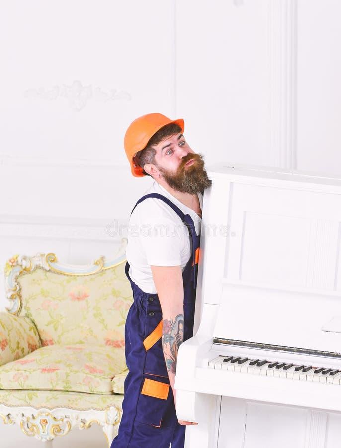 Brodatego robociarza podnośny pianino z wielką siłą Budowniczy usuwa materiał przed domowym odświeżaniem odizolowywającym na biel fotografia royalty free