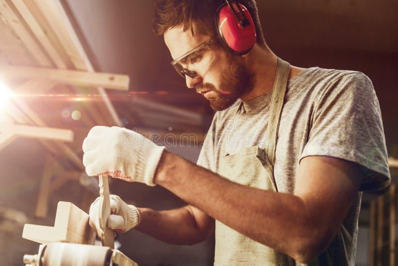 Brodatego rzemieślnika kształtujący drewniany szczegół na pasowym sander obrazy stock