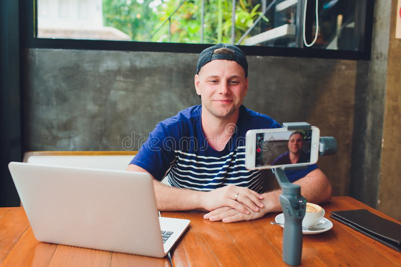 Brodaty atrakcyjny m?ski wideo blogger leje si? dla u?ytkownik?w w eleganckich szk?ach strzela wideo podczas gdy siedz?cy w kawia zdjęcia stock