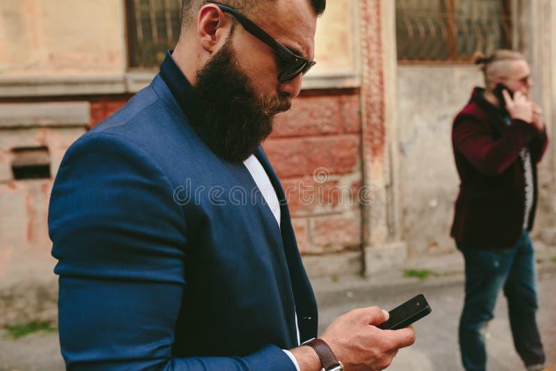 Download Brodaty Biznesmen Patrzeje Telefon Zdjęcie Stock - Obraz złożonej z wysoki, dorosły: 57663102