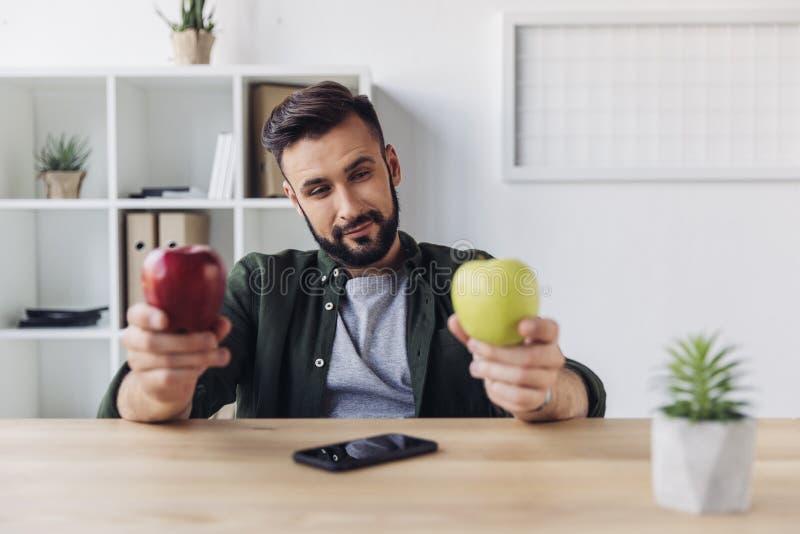 Brodaty biznesmen wybiera między zielonymi i czerwonymi jabłkami podczas gdy siedzący przy biuro stołem fotografia royalty free