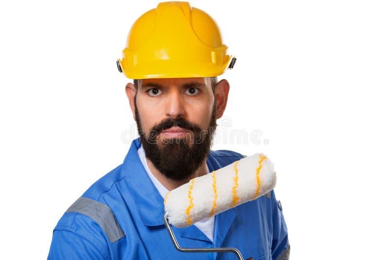 Brodaty budowniczy w żółtym hełma i błękita mienia farby jednolitym rolowniku nad białym tłem zdjęcia stock