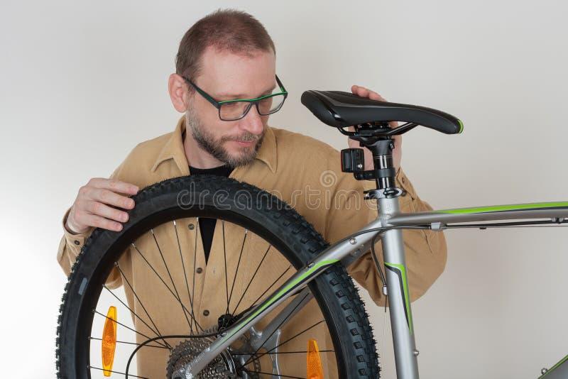 Brodaty caucasian mężczyzna naprawia mtb bicykl fotografia stock