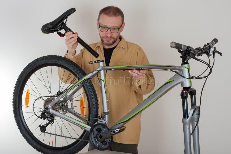 Brodaty caucasian mężczyzna stawia comber na mtb bicyklu obrazy stock