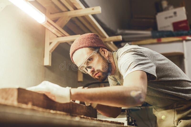 Brodaty cieśla pracuje z kawałkiem drewno obraz royalty free