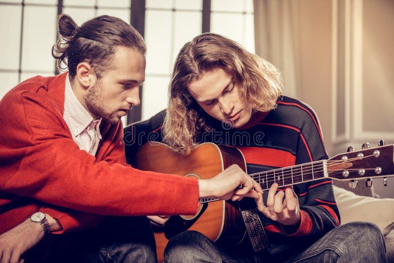 Brodaty gitara adiunkt czuje ruchliwie nauczanie jego utalentowany uczeń zdjęcie royalty free