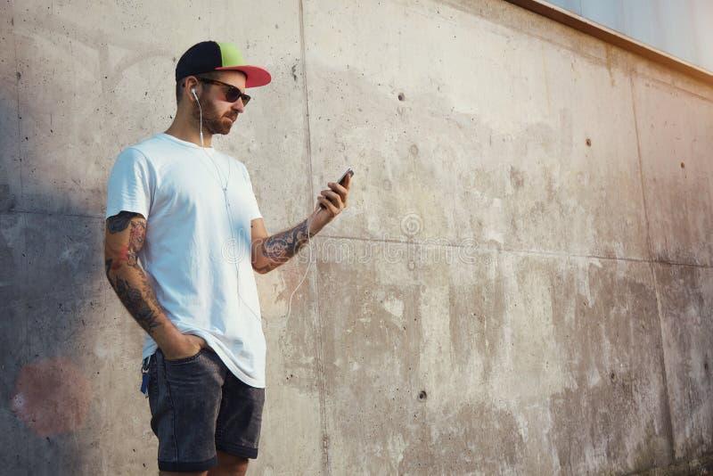 Brodaty i tatuujący młody człowiek trzyma jego smartphone obraz royalty free
