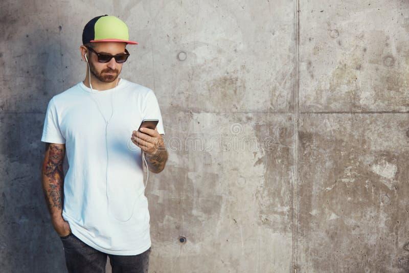 Brodaty i tatuujący młody człowiek trzyma jego smartphone fotografia stock