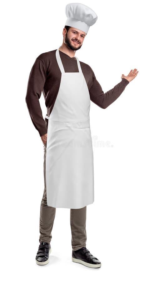 Brodaty kucharz jest ubranym, robi zapraszającemu gestowi na białym tle i kapelusz i fartucha obraz stock