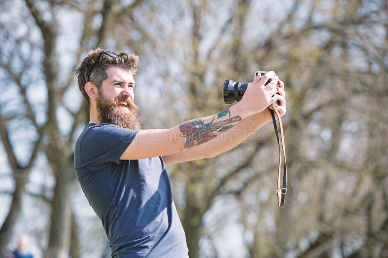 Brodaty mężczyzna bierze selfie na rocznik kamerze Mężczyzna z brodą i wąsy na rozochoconej twarzy, gałąź na tle zdjęcia royalty free