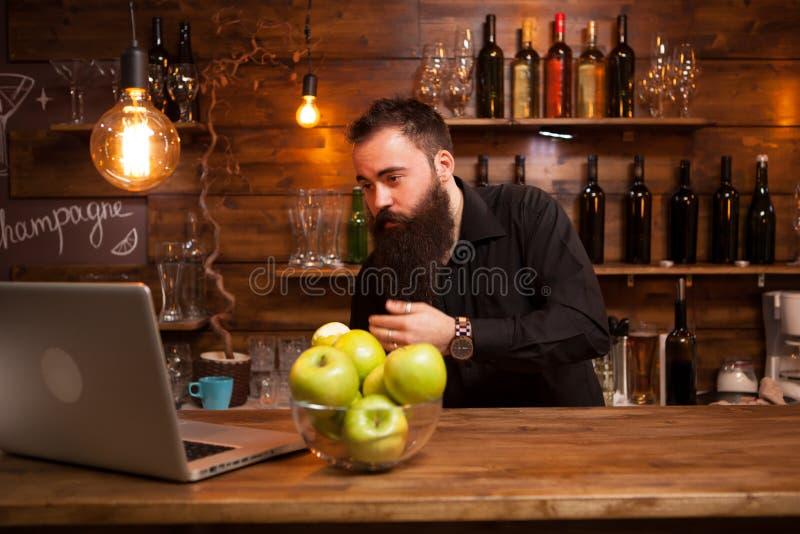 Brodaty młody barman ono sprawdza w laptopie obrazy royalty free