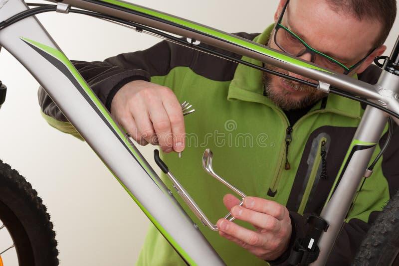 Brodaty mężczyzna śrubuje właściciela bidon na mtb bicycl zdjęcia stock
