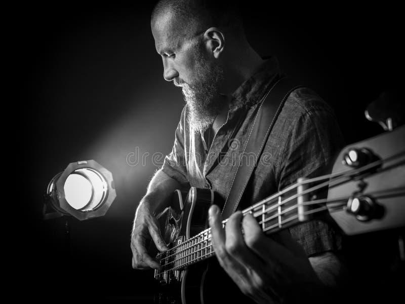 Brodaty mężczyzna bawić się basową gitarę na scenie zdjęcia royalty free