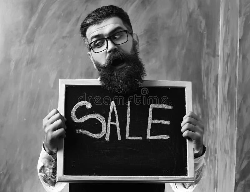Brodaty mężczyzna, brutalna caucasian modnisia mienia sprzedaży inskrypcja na blackboard fotografia royalty free