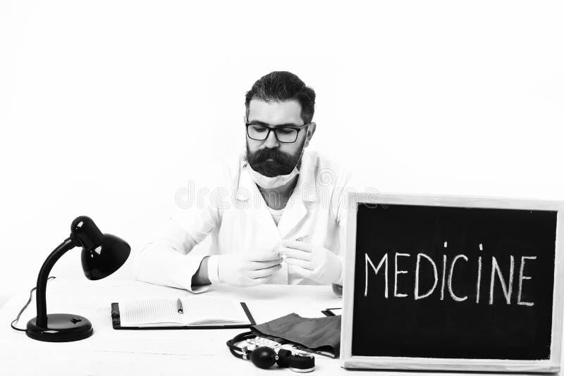 Brodaty mężczyzna, długa broda Brutalnego caucasian doktorski lub nieogolony modniś w masce, medyczny togi obsiadanie przy stołem obrazy stock