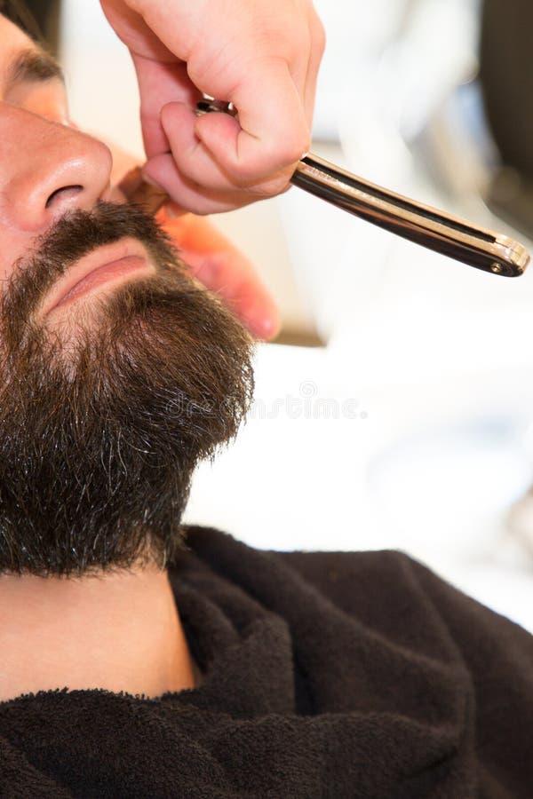 Brodaty mężczyzna Dostaje brody ostrzyżenie fryzjerem męskim w zakładzie fryzjerskim zdjęcia royalty free