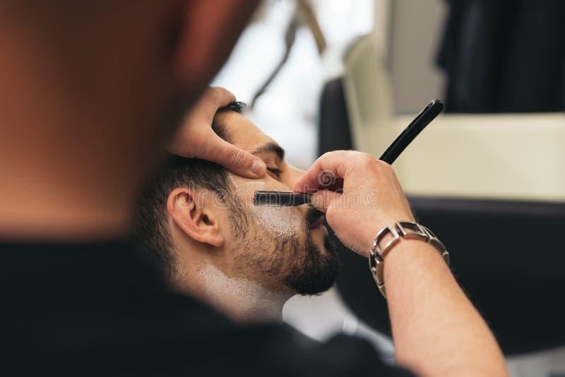 Brodaty mężczyzna Dostaje brody ostrzyżenie Z żyletką fryzjerem męskim zdjęcia stock