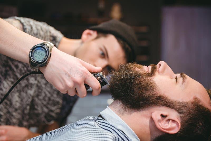 Brodaty mężczyzna dostaje jego brodę golił nowożytnym fryzjerem męskim obraz royalty free