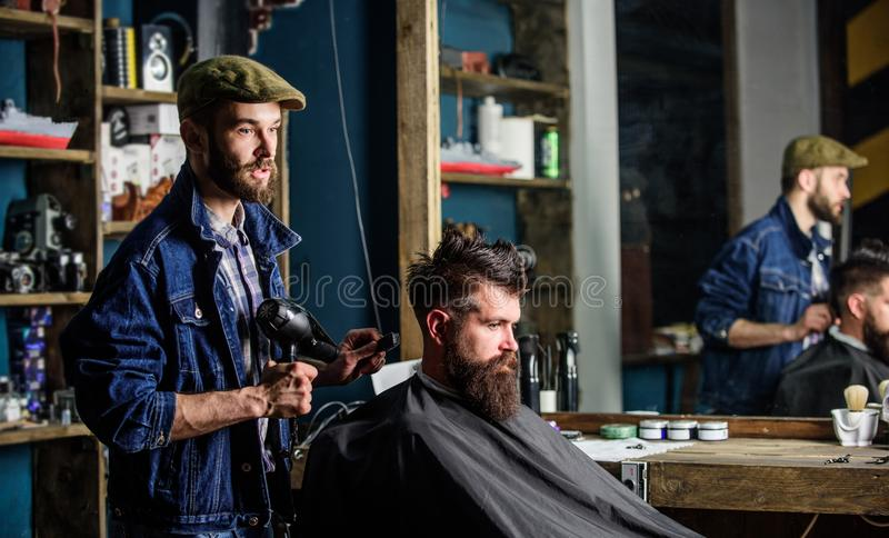 Brodaty mężczyzna dostaje przygotowywający przy fryzjerem z włosianą suszarką podczas gdy siedzący w krześle przy zakładem fryzje zdjęcie stock