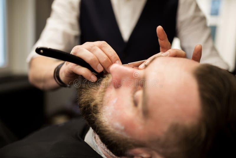 Brodaty mężczyzna goli fryzjerem męskim zdjęcia royalty free