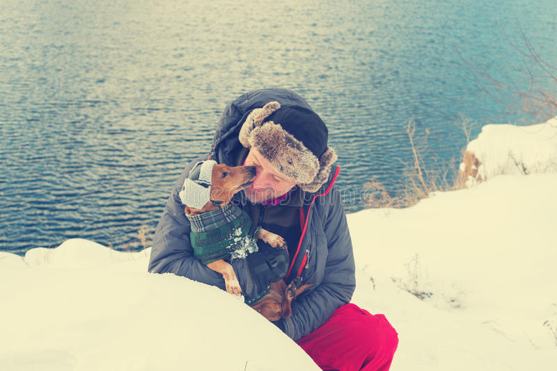 Brodaty mężczyzna i mały pies w śmiesznych zima kapeluszach obrazy royalty free