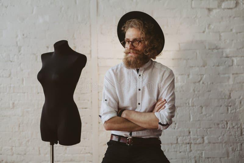 Brodaty mężczyzna jest ubranym kapelusz, koszula, szkieł siedzieć obraz royalty free