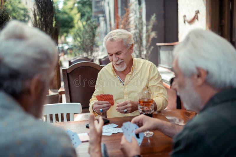 Brodaty mężczyzna jest ubranym pierścionki uprawia hazard z przyjaciółmi zdjęcia royalty free