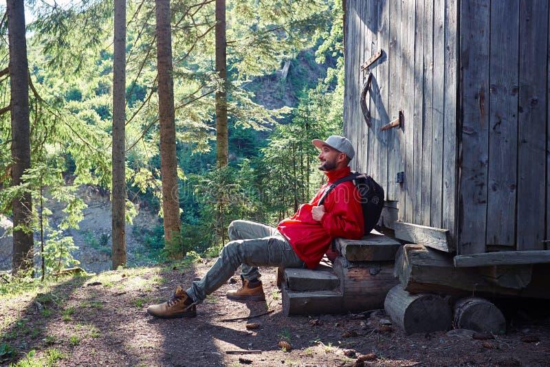 Brodaty mężczyzna obsiadanie na schodkach drewniany dom zdjęcie stock