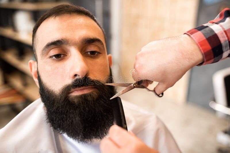 Brodaty mężczyzna obsiadanie w zakładzie fryzjerskim obrazy royalty free