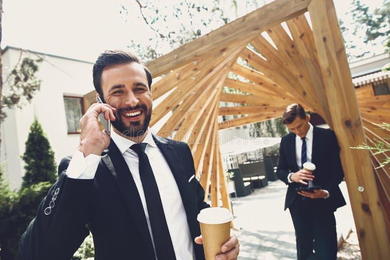 Brodaty mężczyzna rozmawiający przez telefon i jego przyjaciel stojący z tabletem fotografia royalty free
