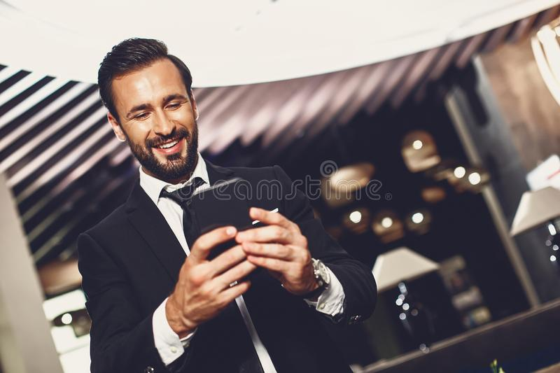 Brodaty mężczyzna stojÄ…cy sam i patrzÄ…cy na ekran swojego nowoczesnego smartfona zdjęcia royalty free