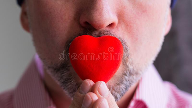 Brodaty mężczyzna trzyma czerwonego serce z palcami na jego wargach, zakończenie w górę fotografia stock
