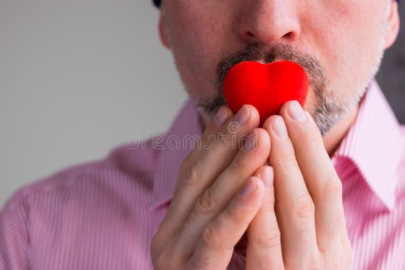Brodaty mężczyzna trzyma czerwonego serce z palcami na jego wargach, zakończenie w górę zdjęcia stock