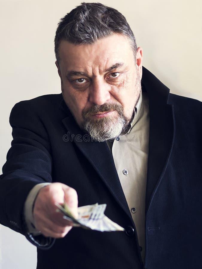 Brodaty mężczyzna w czarnym kostiumu daje pieniądze corruptness Bezprawne operacje fotografia royalty free