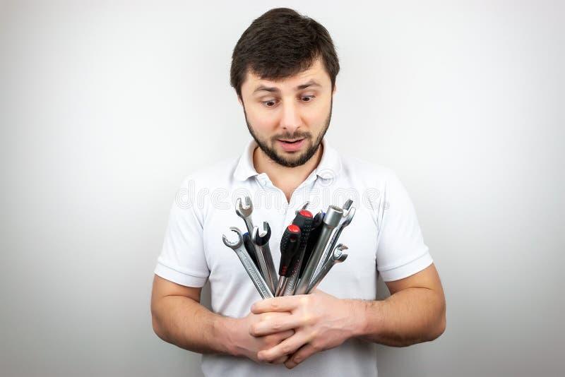 Brodaty mężczyzna w koszulki białych spojrzeniach zaskakujących przy bukietem wyrwania i śrubokręty zdjęcie stock