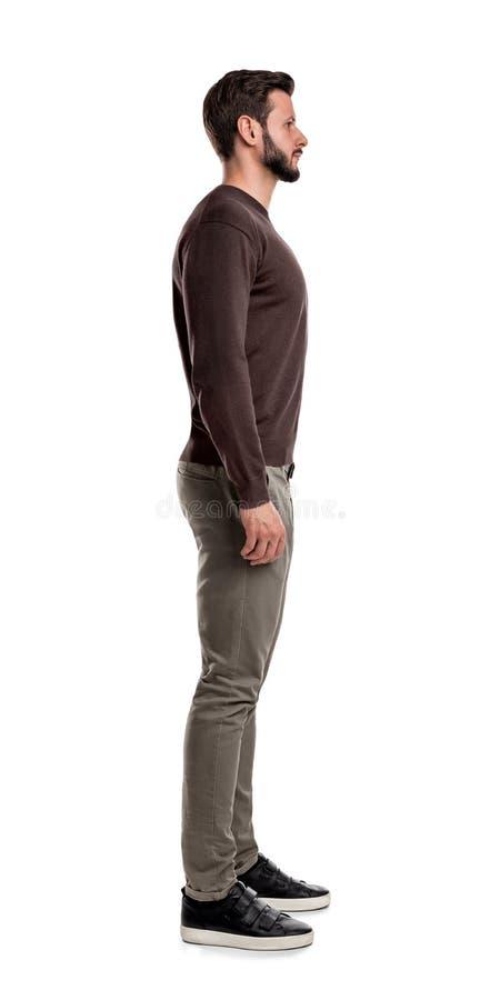 Brodaty mężczyzna w przypadkowych ubraniach stoi wciąż z rękami wiesza prosto na jego stronach w bocznym widoku obrazy stock