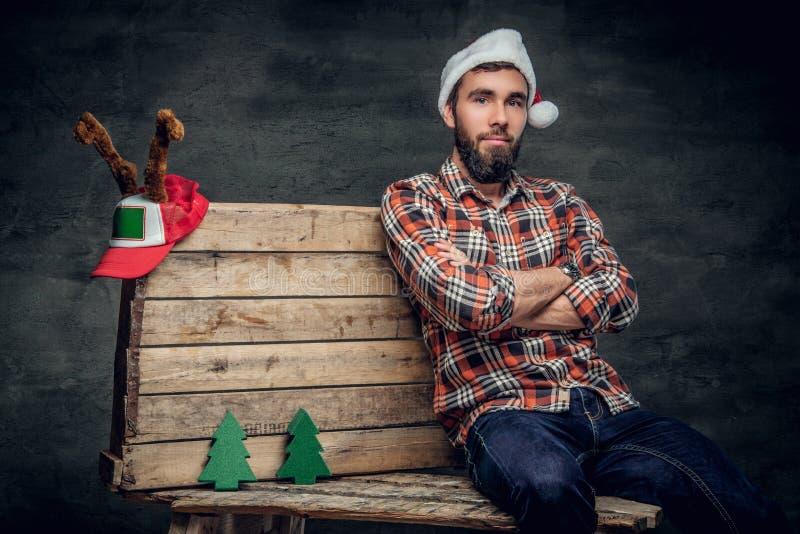 Brodaty mężczyzna w Santa ` s kapeluszu siedzi na drewnianej palecie z jedlinowymi drzewami zdjęcie royalty free