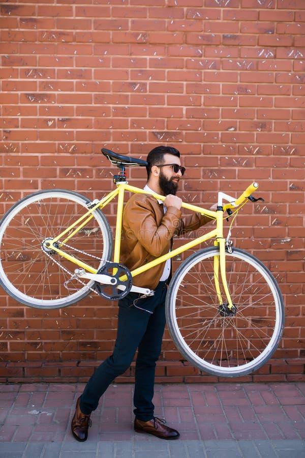 Brodaty mężczyzna z fixie bicyklem Ufny młody brodaty mężczyzna niesie jego bicykl na naramiennej i patrzeje kamerze podczas gdy  zdjęcia stock